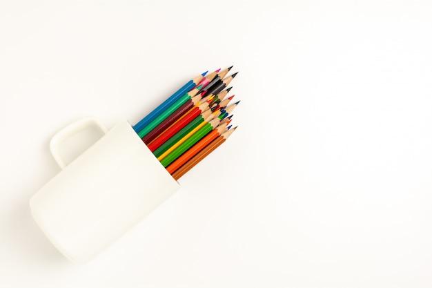 Lápis de cor em uma xícara de café sobre fundo branco