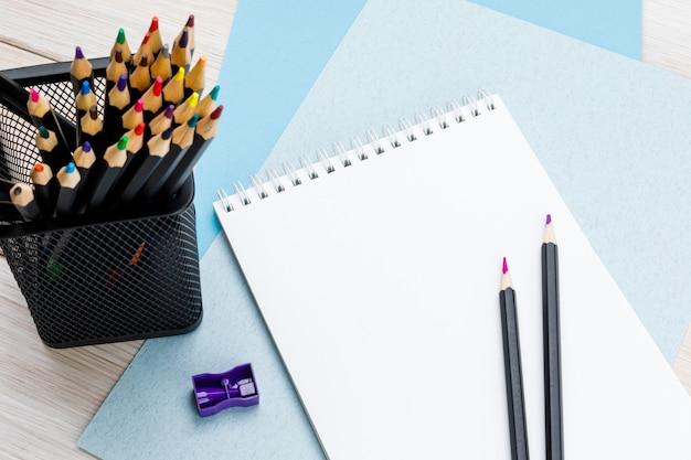 Lápis de cor em uma xícara preta de escritório, apontador roxo, um par de lápis afiados e um caderno em folhas de papelão colorido