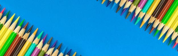 Lápis de cor escolar com faixa colorida de borda longa com espaço de cópia, plano de fundo azul da área de trabalho, foto de vista superior
