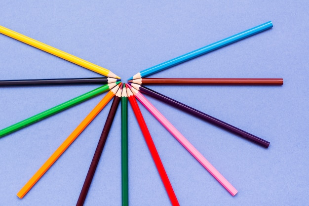 Lápis de cor estão espalhados em uma vista superior azul