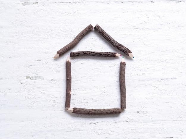 Lápis de cor feitos de arranjo de madeira de natureza como forma de casa