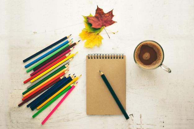 Lápis de cor, folhas secas e papel. moldura para texto. vista de cima. composição de outono. treinamento.