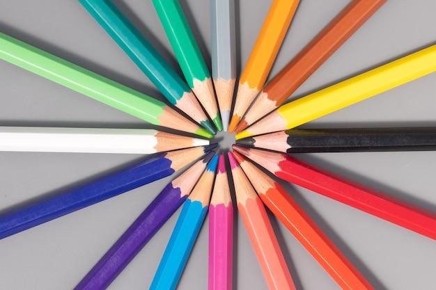 Lápis de cor formando um círculo em fundo cinza