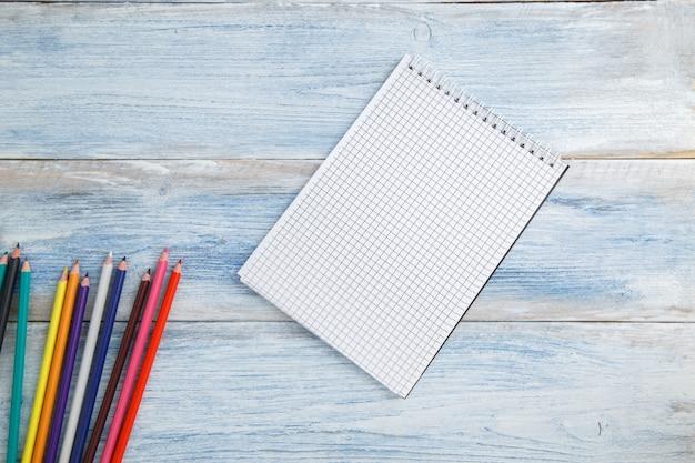 Lápis de cor, giz de cera e bloco de notas em madeira vintage azul e branca arranhada, vista superior