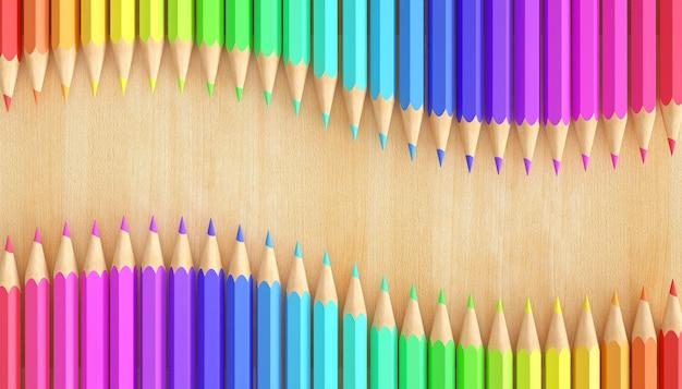 Lápis de cor gradiente em fundo de madeira natural.