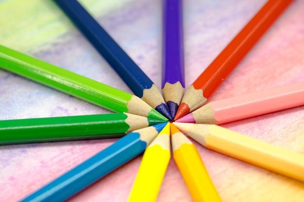 Lápis de cor grandes empilhados em um close de círculo em um fundo colorido com lápis de cor