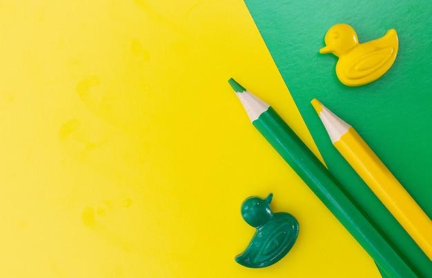 Lápis de cor isolados em fundo verde e amarelo close-up