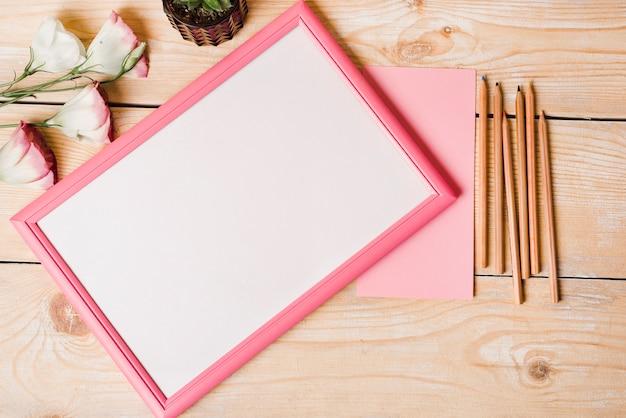 Lápis de cor; papel; eustoma flores e moldura branca com borda rosa na mesa de madeira