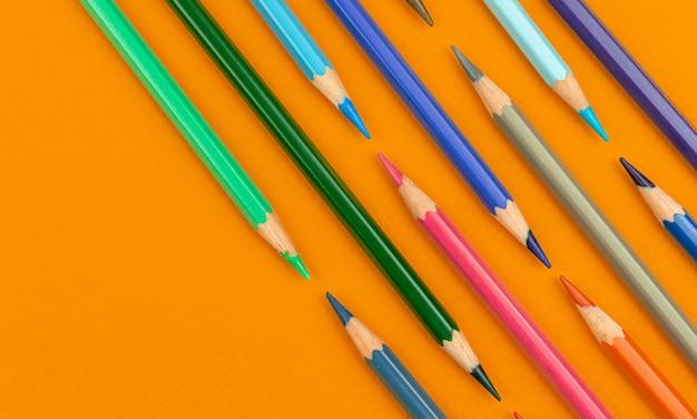 Lápis de cor plana lay fundo criativo, foto laranja vista superior da mesa