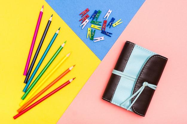 Lápis de cor, prendedores de roupa coloridos e organizador em uma superfície tricolor