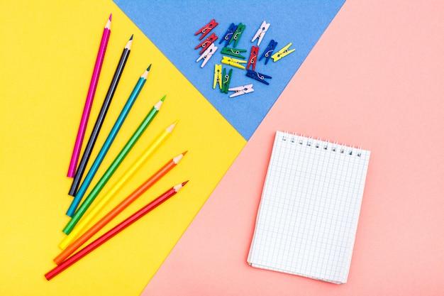 Lápis de cor, prendedores de roupa coloridos e um bloco de notas em um fundo tricolor