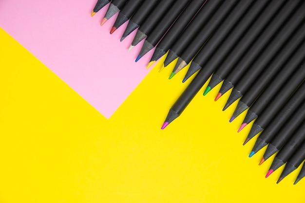 Lápis de cor preta em tons de rosa e amarelo sobre fundo de papel de cor