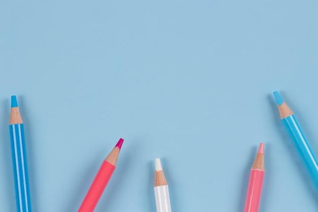 Lápis de cor sobre fundo azul claro cores brancas rosa pastel vista superior