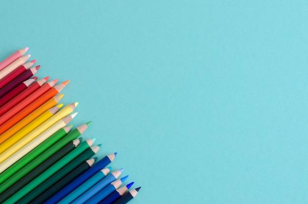Lápis de cor sobre fundo azul, com espaço para escrever.
