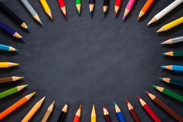 Lápis de cor sobre fundo de quadro de giz