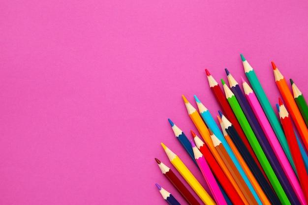 Lápis de cor sobre fundo rosa, com espaço de cópia de texto.