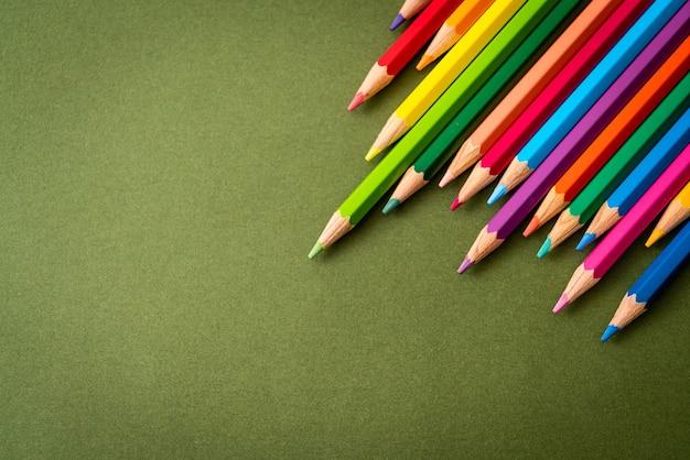 Lápis de cor sobre fundo verde com espaço de cópia