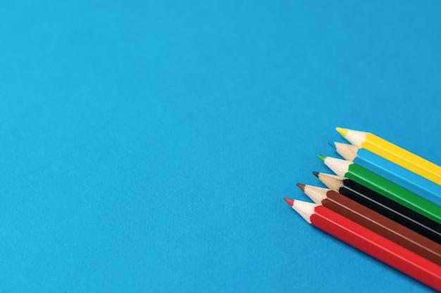Lápis de cor sobre um fundo azul brilhante. papelaria e material escolar.