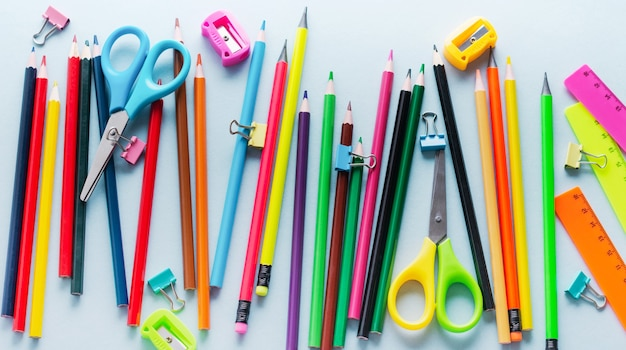 Lápis de cor, tesoura, caderno, régua, caneta, borracha, apontador e muito mais em vidro. escola e artigos de papelaria do escritório na mesa azul clara. conceito de volta às aulas. vista do topo.