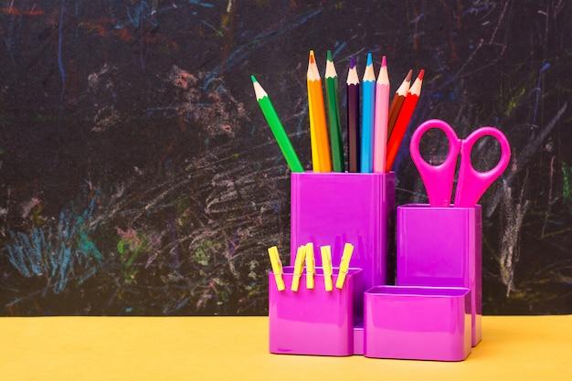 Lápis de cor, tesouras e clipes em um copo para artigos de papelaria em uma mesa