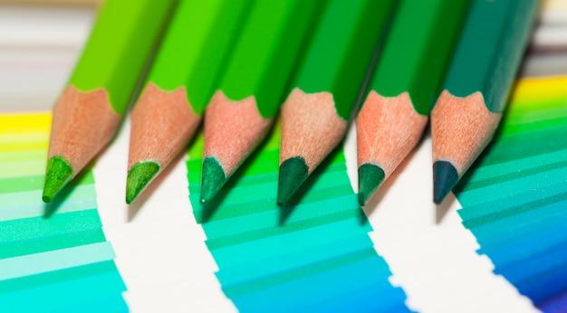 Lápis de cor verde e cartela de cores de todas as cores
