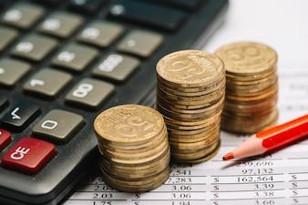 Lápis de cor vermelha com calculadora e pilha de moedas sobre o relatório financeiro