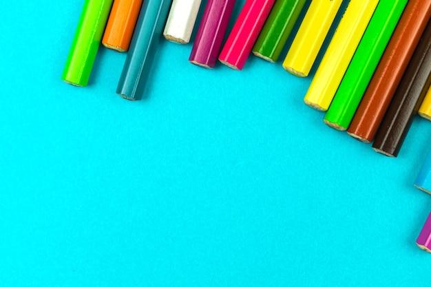 Lápis de cores diferentes sobre uma foto brilhante da vista de cima da mesa do desktop, conceito de plano de fundo de papelaria escolar