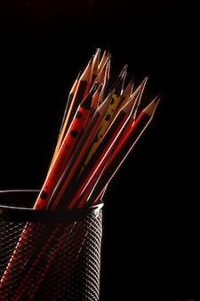 Lápis de grafite para desenhar e escrever alinhados dentro de uma pequena cesta preta oon preto