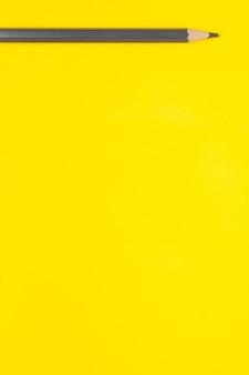 Lápis de madeira afiado cinza horizontal em um fundo amarelo brilhante, isolado, cópia espaço, simulação