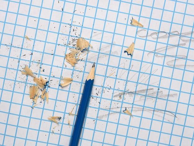 Lápis de madeira afiado com aparas em uma folha de papel quadriculada