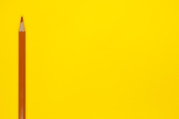 Lápis de madeira afiado marrom claro vertical sobre um fundo amarelo brilhante, isolado, cópia espaço, simulação de