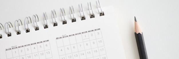 Lápis de madeira afiado perto do calendário de papel para close-up