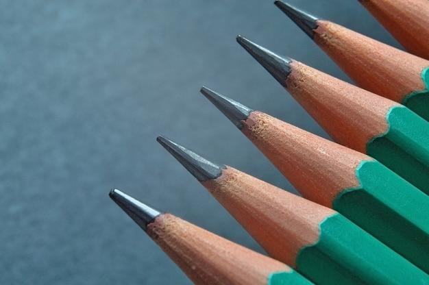 Lápis de madeira afiados verdes com grafite preta sobre fundo escuro texturizado. fechar-se.