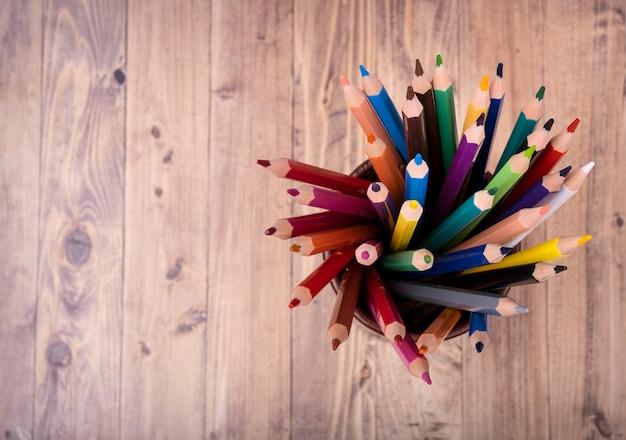 Lápis de madeira coloridos, em um copo de couro marrom, visto de cima,