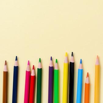 Lápis de madeira coloridos para a escola em fundo de papel amarelo. artigos de papelaria da escola e do escritório no fundo amarelo. conceito de volta às aulas. imagem quadrada. vista do topo.