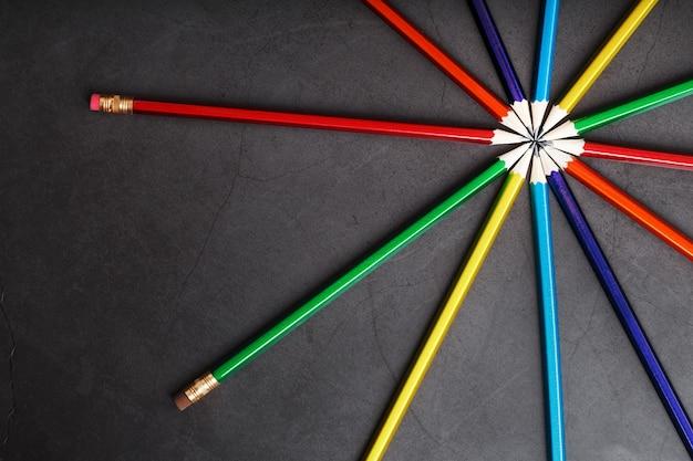 Lápis de madeira de diferentes cores em forma de estrela sobre fundo preto. vista do topo