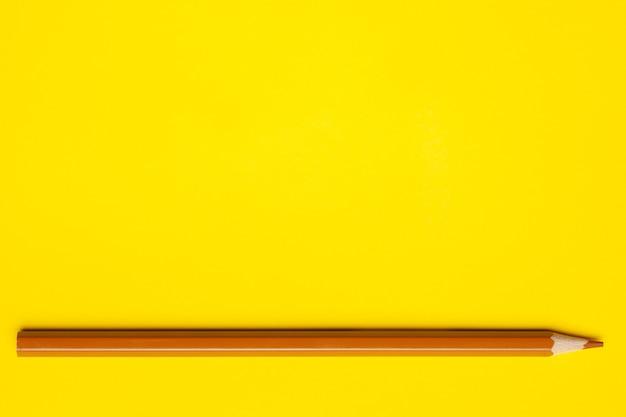 Lápis de madeira pontiagudo castanho claro horizontal sobre fundo amarelo brilhante, isolado, espaço de cópia, simulação