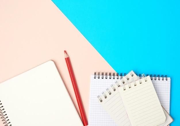 Lápis de madeira vermelho e pilha de cadernos abertos em espiral com lençóis brancos em branco