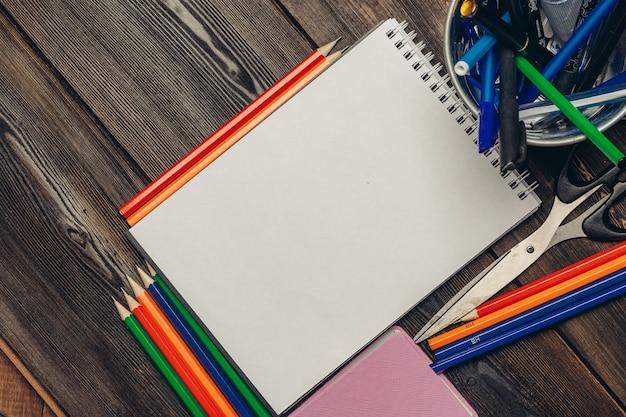Lápis de papelaria de blocos de notas na escola de desenho de negócios de escritório de mesa de madeira.