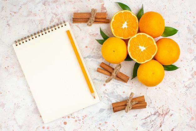 Lápis de paus de canela em bloco de notas de mandarinas frescas na vista superior na superfície isolada brilhante