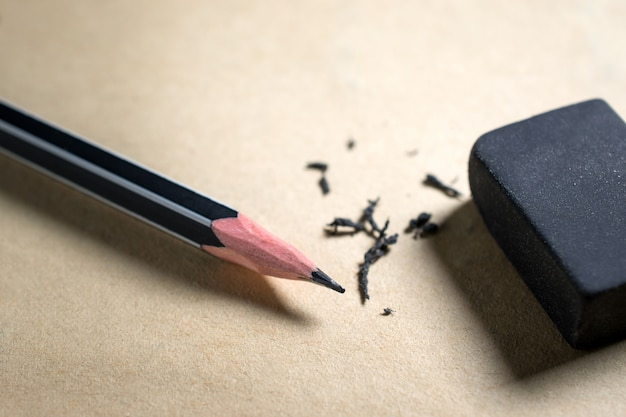 Lápis e borracha em papel marrom erro, risco, apagar.
