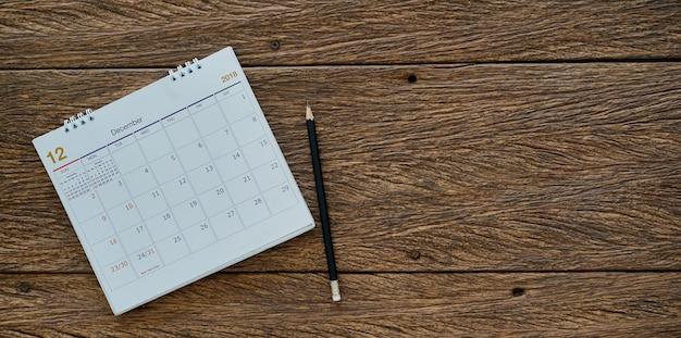 Lápis e calendário no fundo de madeira