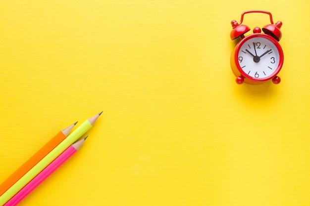 Lápis e despertador coloridos brilhantes no amarelo.