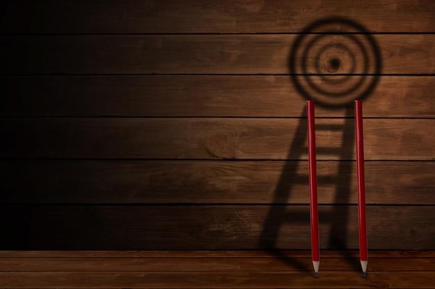 Lápis e escada com sombra de placa de destino em fundo de madeira, desafio na realização do objetivo de negócios e conceito de sucesso.