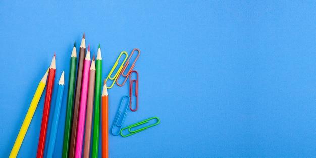 Lápis e grampos coloridos do pastel no fundo azul.