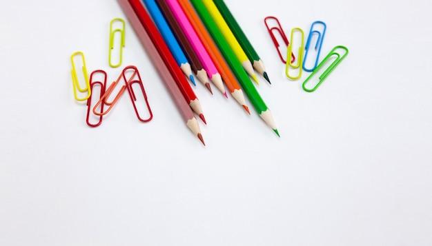 Lápis e grampos coloridos do pastel no fundo branco.
