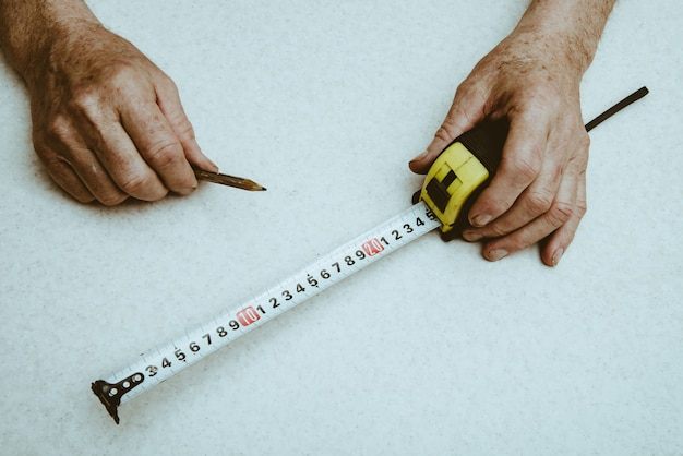 Lápis e roleta nas mãos do idoso trabalhador