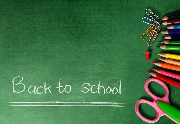 Lápis e tesouras de cor com um fundo verde. conceito de volta às aulas