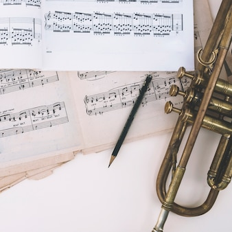 Lápis e trompete perto de partituras