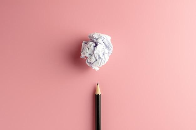 Lápis e uma bola de papel amassado em papel rosa.